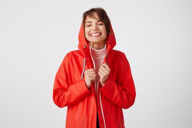 Portret van jonge mooie gelukkige kortharige dame in rode regenjas, ogen geopend en breed lachend, geniet van het leven. staand.