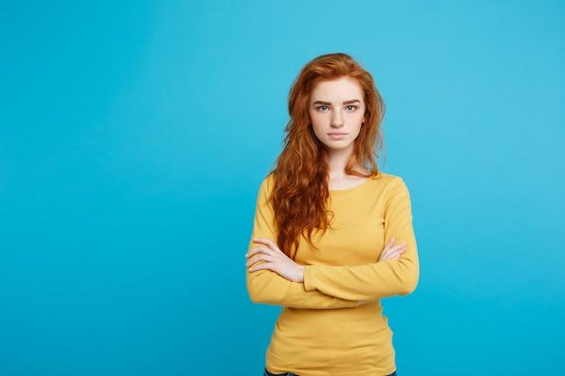 Portret van jonge mooie gembervrouw met teder ernstig gezicht die wapens kruisen die op het exemplaarruimte van de pastelkleurblauwe muur worden geïsoleerd