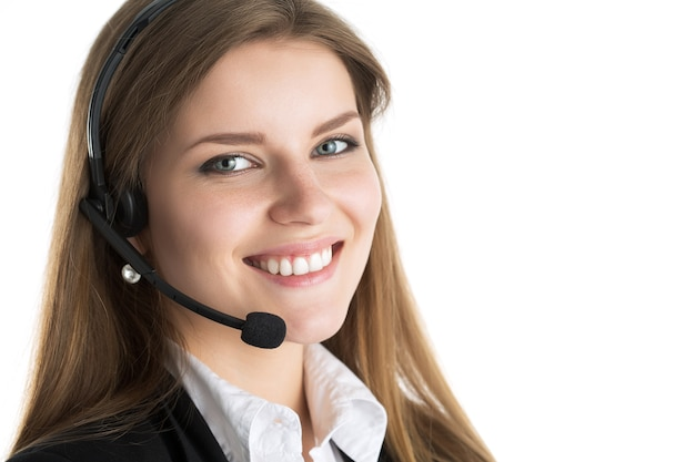 Portret van jonge mooie glimlachende call centre werknemer die met iemand spreekt. glimlachende klantondersteuningsexploitant op het werk