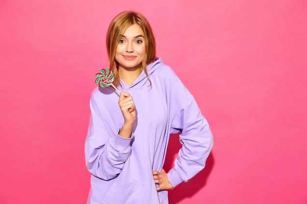 Portret van jonge mooie glimlachende hipster vrouw in trendy zomer hoodie. het sexy onbezorgde vrouw stellen dichtbij roze muur. positief model met lolly