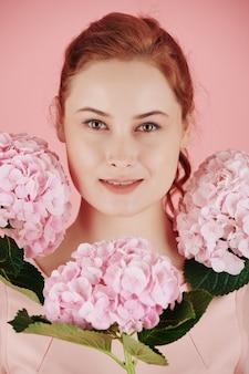 Portret van jonge mooie glimlachende roodharige vrouw met mooie pinnk bloemen rond