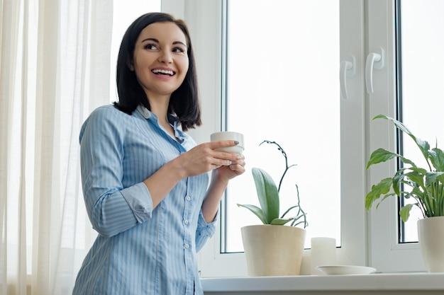 Portret van jonge mooie glimlachende vrouw met kop van koffie