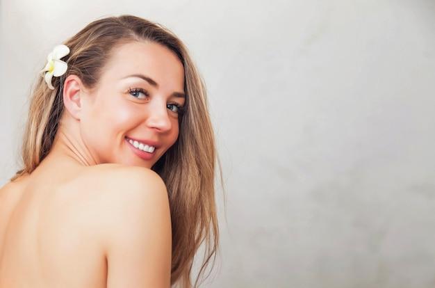 Portret van jonge mooie half naakte vrouw met bloem voor advertenties beauty spa of massagesalon. portret van lachende jonge topless vrouwelijke middelbare leeftijd oud op grijze achtergrond. gezondheid, jeugd en schoonheidsconcept
