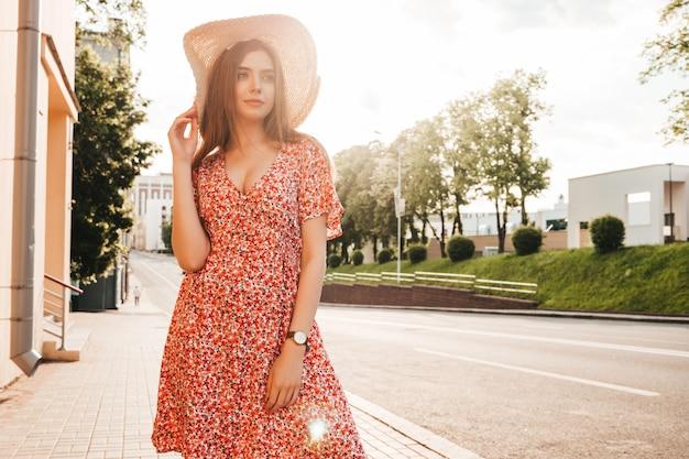 Portret van jonge mooie hipster meisje in trendy zomer zonnejurk. sexy zorgeloos vrouw die zich voordeed op straat achtergrond in hoed bij zonsondergang. positief model buitenshuis