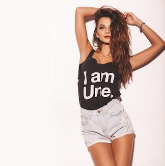 Portret van jonge mooie hipster meisje in trendy zomer zwart t-shirt en jeans shorts. sexy onbezorgde die vrouw op wit wordt geïsoleerd. donkerbruin model met make-up en kapsel