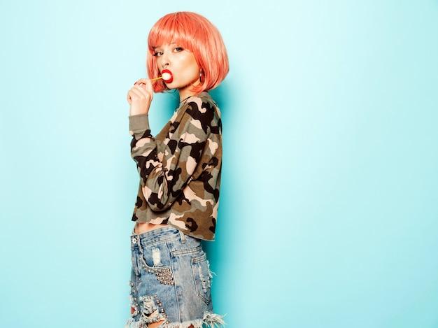 Portret van jonge mooie hipster slecht meisje in trendy jeans broek en oorbel in haar neus. positief model likken ronde kandijsuiker