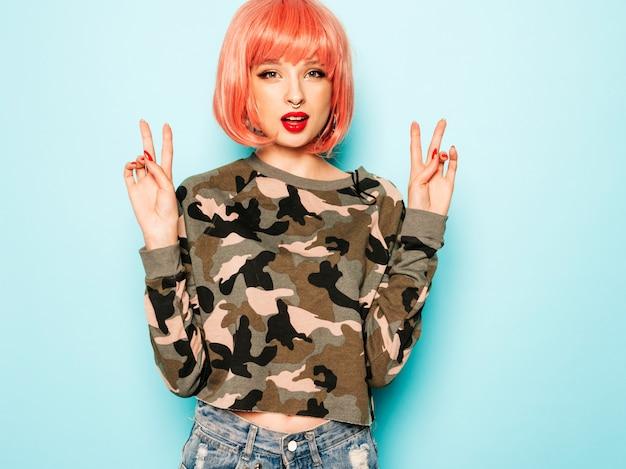 Portret van jonge mooie hipster slecht meisje in trendy jeans broek en oorbel in haar neus. sexy zorgeloos lachende vrouw poseren in studio in roze pruik. positief model plezier. toont vredesteken