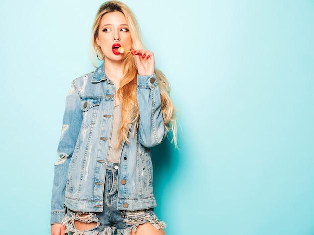 Portret van jonge mooie hipster slecht meisje in trendy jeans kleding en oorbel in haar neus. positief model dat rond suikersuikergoed likt