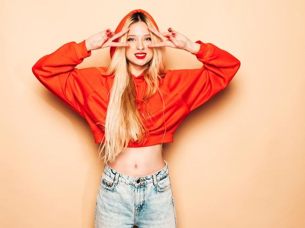 Portret van jonge mooie hipster slecht meisje in trendy rode hoodie en oorbel in haar neus. positief model vertoont vredesteken