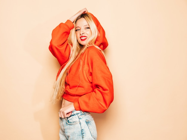 Portret van jonge mooie hipster slecht meisje in trendy rode hoodie en oorbel in haar neus. positief model