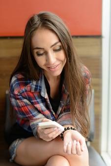 Portret van jonge mooie hipster vrouw ontspannen in de coffeeshop binnenshuis
