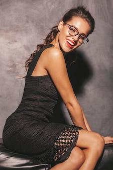 Portret van jonge mooie hipstervrouw in trendy de zomer zwarte kleding. het sexy onbezorgde vrouw stellen dichtbij muur. donkerbruin model met make-up en kapsel
