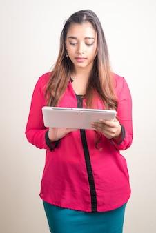Portret van jonge mooie indiase zakenvrouw met behulp van digitale tablet