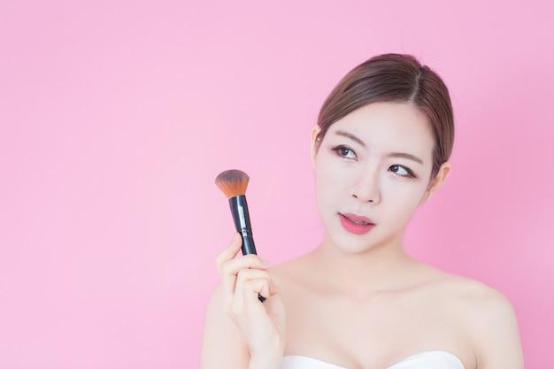 Portret van jonge mooie kaukasische aziatische vrouw die kosmetisch borstelpoeder toepast. cosmetologie, huidverzorging, gezicht reinigen