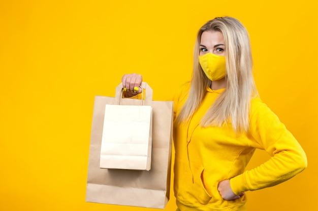 Portret van jonge mooie kaukasische blonde vrouw met papieren eco tas in geel beschermend masker geïsoleerd,