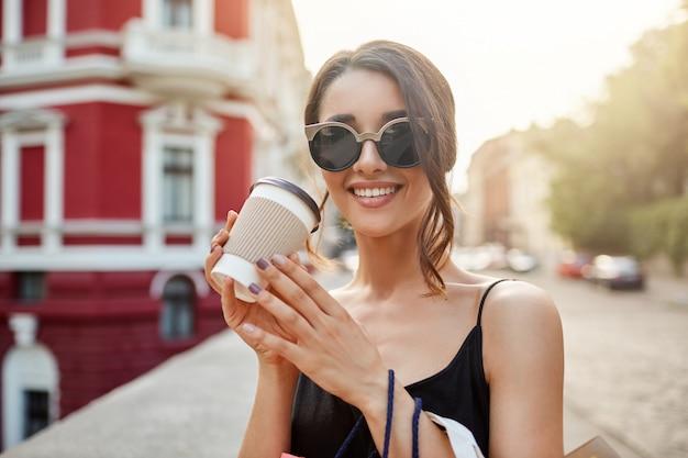 Portret van jonge mooie kaukasische meisje met donker haar in zonnebril en zwarte jurk lachend met tanden, koffie drinken, ontspannen na lang winkelen in winkelcentrum verliezen.
