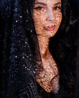 Portret van jonge mooie kaukasische meisje met zwarte sluier en met schaduw op het eerste gezicht