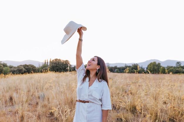 Portret van jonge mooie kaukasische vrouw die in openlucht bij zonsondergang op een geel gebied loopt. draagt een moderne hoed en glimlacht. geluk concept