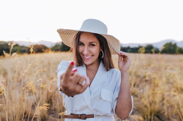 Portret van jonge mooie kaukasische vrouw in openlucht bij zonsondergang op een geel gebied. draagt een moderne hoed en glimlacht. een gebaar van me maken met wijsvinger