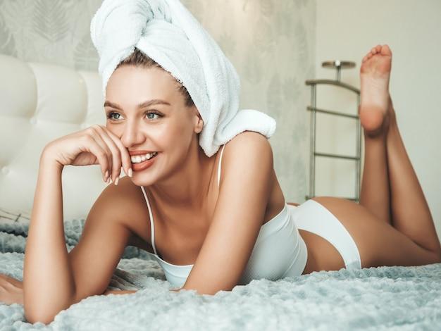 Portret van jonge mooie lachende vrouw in witte lingerie en handdoek op hoofd