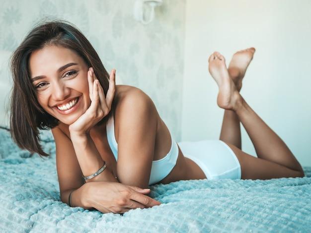 Portret van jonge mooie lachende vrouw in witte lingerie