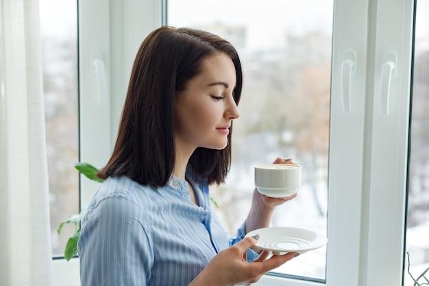 Portret van jonge mooie lachende vrouw met kopje koffie in blauw shirt bij het raam