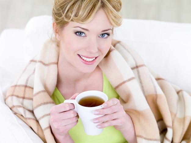 Portret van jonge mooie lachende vrouw met warme kop koffie - hoge hoek