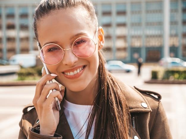 Portret van jonge mooie lachende vrouw spreken op telefoon trendy meisje in casual zomer kleding grappig en positief vrouw die zich voordeed op straat