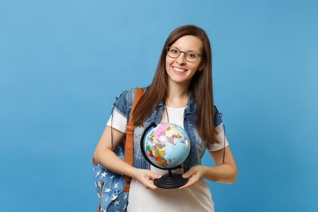 Portret van jonge mooie lachende vrouw student in glazen met rugzak met wereldbol en leren geografie geïsoleerd op blauwe achtergrond. onderwijs in het concept van de middelbare schooluniversiteit.
