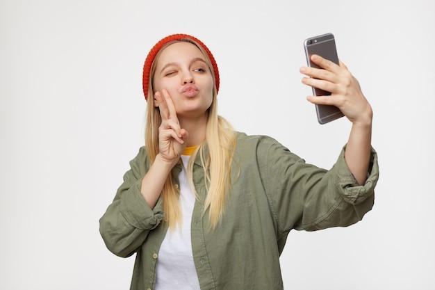 Portret van jonge mooie langharige blonde vrouw die haar lippen nastreeft en knipoogt terwijl ze portret van zichzelf maakt en overwinning gebaar toont, poseren op blauw