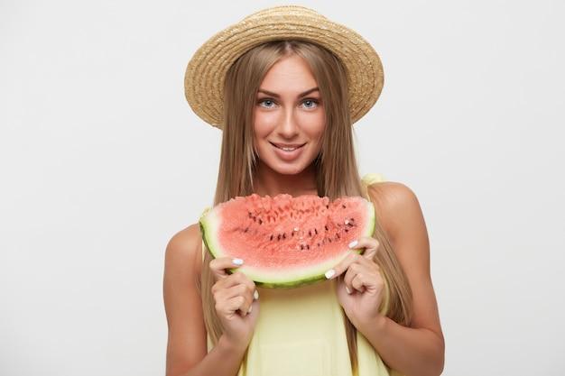 Portret van jonge mooie langharige dame met casual kapsel postively kijken naar camera met charmante glimlach terwijl poseren op witte achtergrond met watermeloen