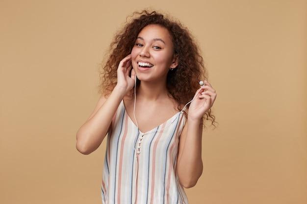 Portret van jonge mooie langharige krullende brunette vrouw die gelukkig lacht tijdens het luisteren naar muziek in haar koptelefoon, geïsoleerd op beige