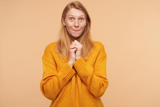 Portret van jonge mooie langharige vrouw met groene ogen die haar lippen bijt en opgeheven handen vouwt terwijl ze op beige in mosterdtrui staat