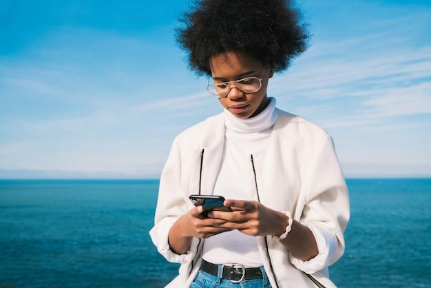 Portret van jonge mooie latijns-vrouw met behulp van haar mobiele telefoon buitenshuis met de zee aan. technologie en communicatieconcept.