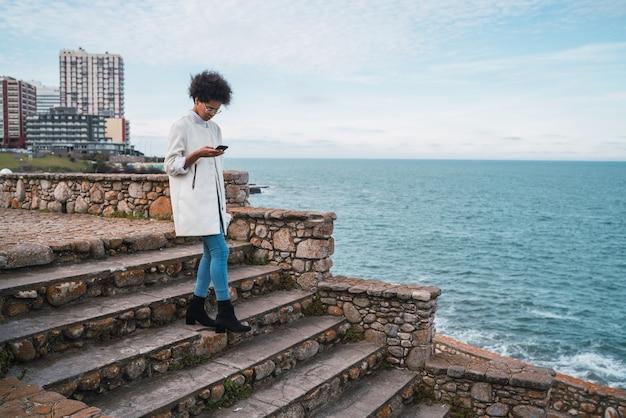 Portret van jonge mooie latijns-vrouw met behulp van haar mobiele telefoon tijdens het wandelen op de kustlijn. technologie en communicatieconcept.