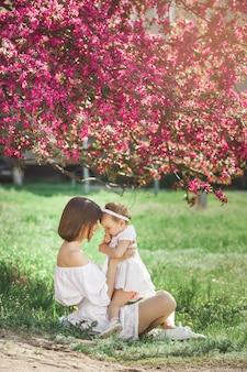 Portret van jonge mooie moeder met haar kleine babymeisje. sluit nog steeds van liefhebbende familie. aantrekkelijke vrouw die haar kind in roze bloemen en het glimlachen houdt.