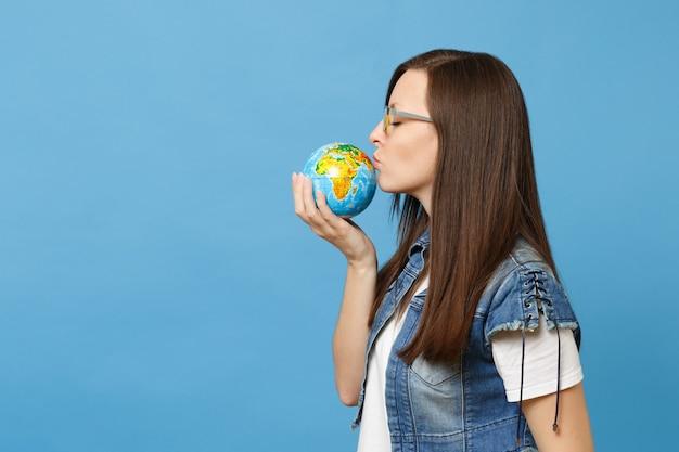 Portret van jonge mooie ontspannen rustige vrouw student in glazen met kussende wereldbol geïsoleerd op blauwe achtergrond. onderwijs aan de universiteit. red planeet. ecologie milieubescherming concept.