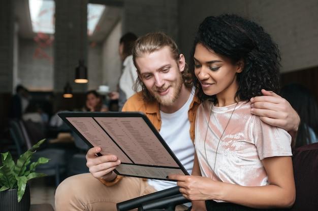 Portret van jonge mooie paar zittend in restaurant met menu in handen