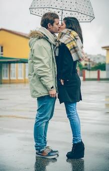 Portret van jonge mooie paar zoenen onder de paraplu in een regenachtige herfstdag. liefde en paar relaties concept.