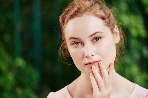 Portret van jonge mooie peinzende vrouw met natuurlijke make-up camera kijken