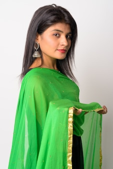 Portret van jonge mooie perzische vrouw die traditionele kleding draagt tegen witte muur