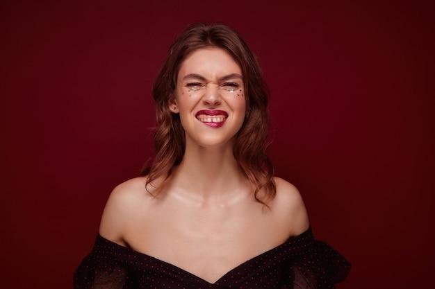Portret van jonge mooie positieve vrouw met bruin haar haar gezicht fronsen en onderlip bijten tijdens het kijken, gekleed in elegante zwarte top met rode stippen