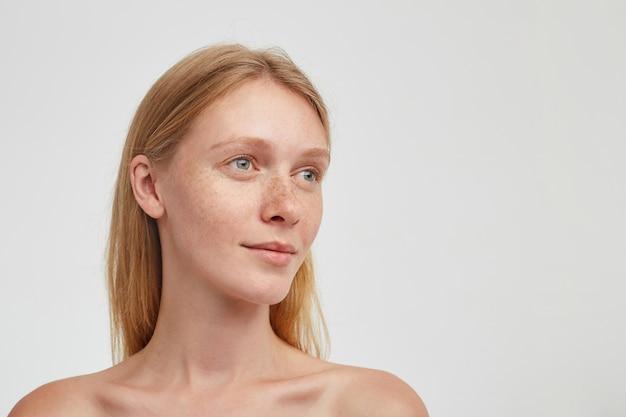 Portret van jonge mooie roodharige vrouw met groene ogen en casual kapsel die bedachtzaam opzij kijkt en haar lippen gevouwen houdt, geïsoleerd over witte muur