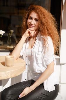 Portret van jonge mooie roodharige vrouw zitten in een café