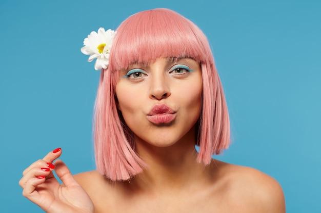 Portret van jonge mooie roze harige vrouw met bob kapsel haar lippen vouwen in lucht kus terwijl positief kijken naar camera, poseren op blauwe achtergrond met opgeheven hand