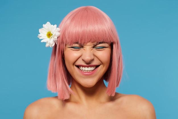 Portret van jonge mooie roze harige vrouw met bob kapsel toont haar perfecte witte tanden terwijl gelukkig lachend met gesloten ogen, geïsoleerd