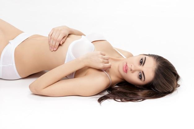 Portret van jonge mooie sensuele vrouw met lange slanke benen in wit ondergoed ligt op rug geïsoleerd