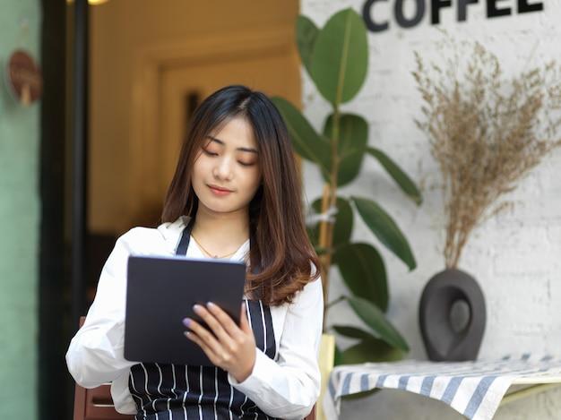 Portret van jonge mooie serveerster die een bestelling op digitale tablet in restaurant neemt