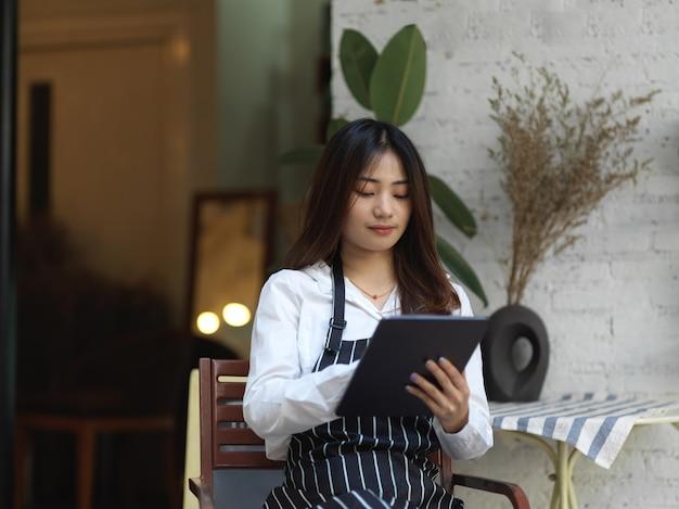 Portret van jonge mooie serveerster die een bestelling op digitale tablet voor café neemt