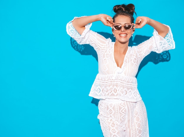 Portret van jonge mooie sexy glimlachende vrouw met lijkenetende kapsel. trendy meisje in casual zomer witte hipster pak kleding in zonnebril. heet model dat op blauw wordt geïsoleerd